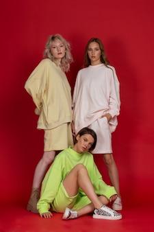 赤いスタジオの背景で一緒にポーズをとるスポーツウェアの3人の魅力的な若い女性
