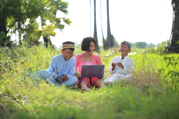 イスラム教徒の服を着た3人の子供が座ってラップトップでインターネットを見て、農園で楽しんでいます。