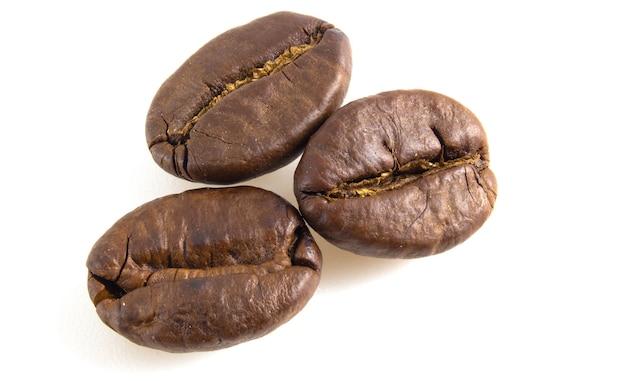 白い背景の上の3つのコーヒー豆。アラビカ種のクローズアップ。