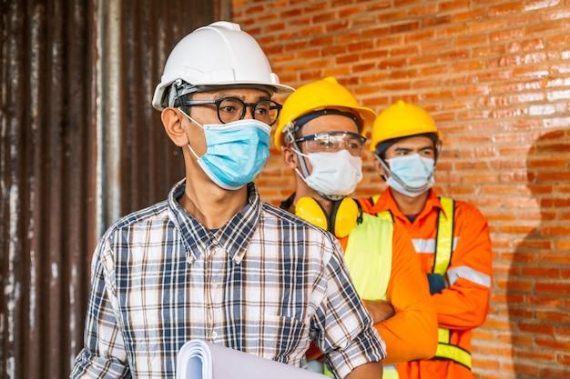 建設エンジニアのチームと3人の建築家が医療用マスクを着用する準備ができています。 coronaまたはcovid-19は、建設の設計時にマスクを着用します。