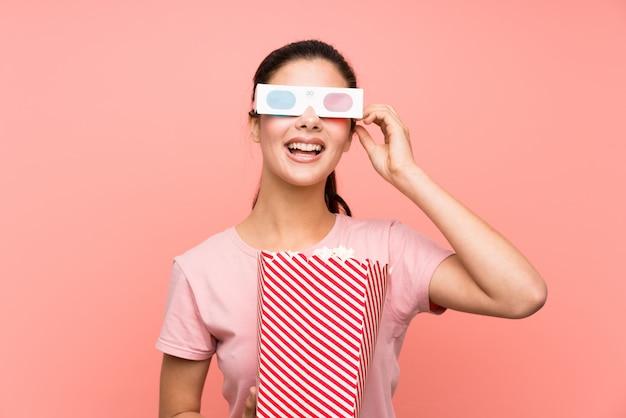 3 dメガネでポップコーンを食べる孤立したピンクの壁の上の10代の女の子