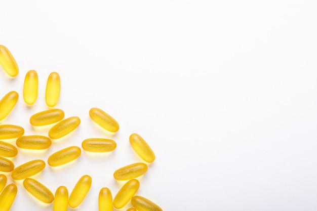 Омега-3 капсулы на белом фоне рыбий жир желтые капсулы витамин d, e, дополнение концепция здравоохранения