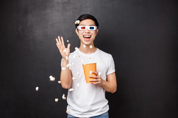 レジャー、映画、ライフスタイルのコンセプト。映画の3 dメガネを見て、映画館の画面でポップコーンを投げるtシャツで面白がって、のんきな面白いアジアの男の肖像、スタンド