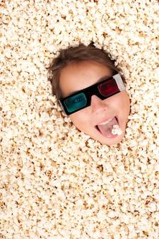 3 dメガネをかけてポップコーンに埋もれている若い女の子