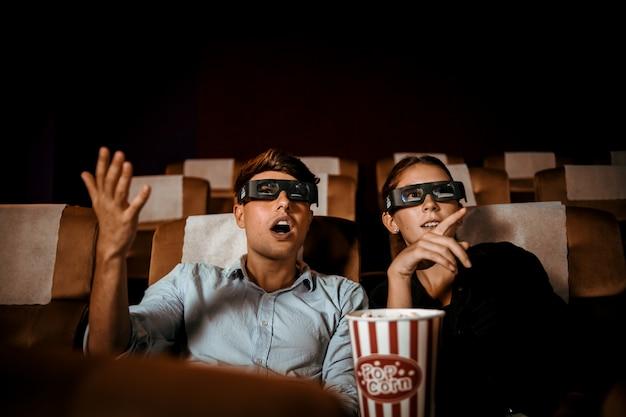 カップルは、ポップコーンの笑顔と幸せそうな顔で劇場で3 d映画を見る