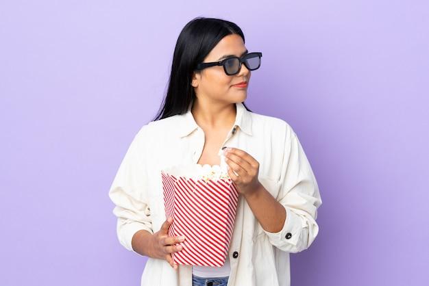 3 dメガネで白い壁に分離され、ポップコーンの大きなバケツを保持している若いラテン女性女性