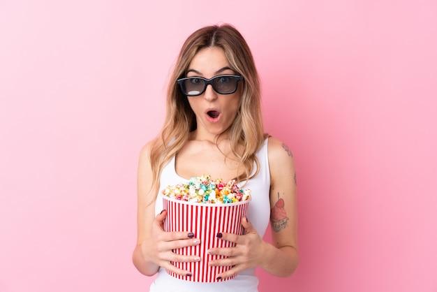 3 dメガネに驚いて、ポップコーンの大きなバケツを保持している孤立したピンクの壁の上の若い女性