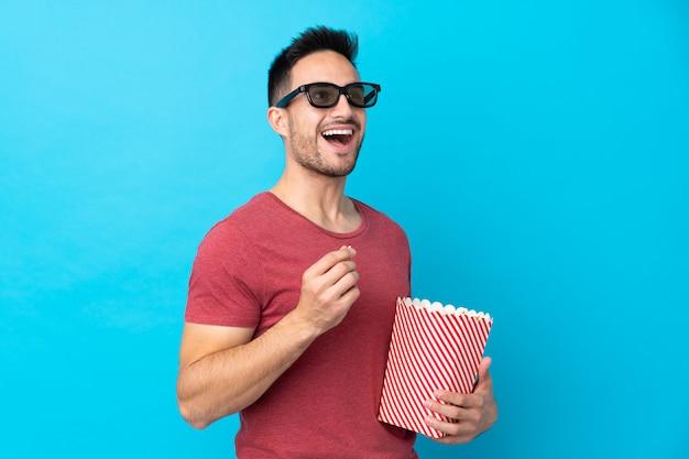 3 dメガネとポップコーンの大きなバケツを保持している分離の青い壁の上の若いハンサムな男