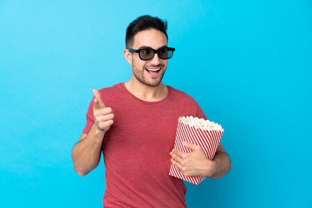 3 dメガネで分離された青い壁の上の若いハンサムな男とポップコーンの大きなバケツを押しながら正面を指す