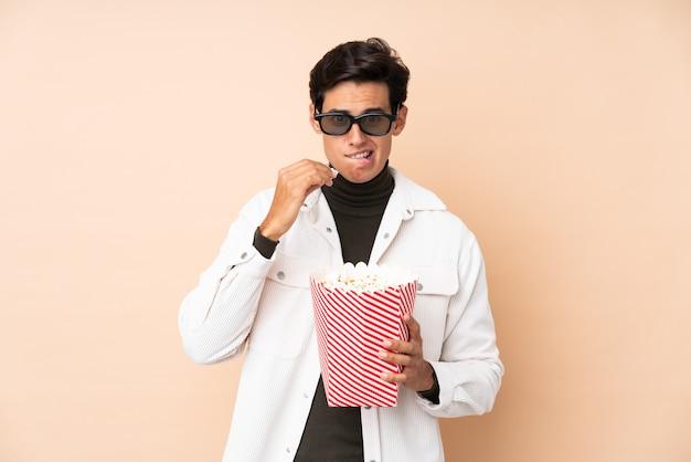 3 dメガネとポップコーンの大きなバケツを保持している壁の上の男