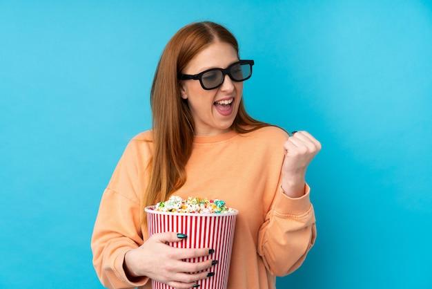 3 dメガネをかけて、側を見ながらポップコーンの大きなバケツを保持している若い赤毛の女性