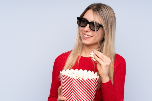 青の3 dメガネとポップコーンの大きなバケツを保持している若いブロンドの女性