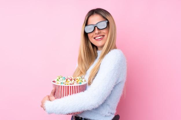 3 dメガネとポップコーンの大きなバケツを保持している孤立したピンクの壁の上の若いウルグアイ女性