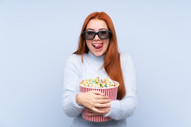 3 dメガネとポップコーンの大きなバケツを保持している分離の青い壁を越えて赤毛ティーンエイジャーの女の子