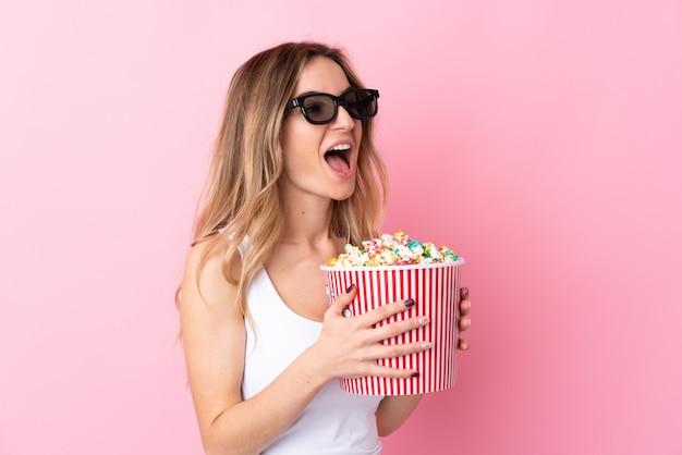 3 dメガネとポップコーンの大きなバケツを保持している若い女性