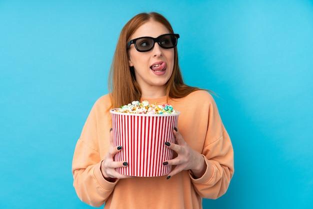 3 dメガネとポップコーンの大きなバケツを保持している若い赤毛の女性