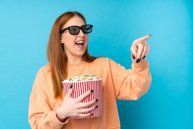 3 dメガネとポップコーンの大きなバケツを押しながらさして若い赤毛の女性