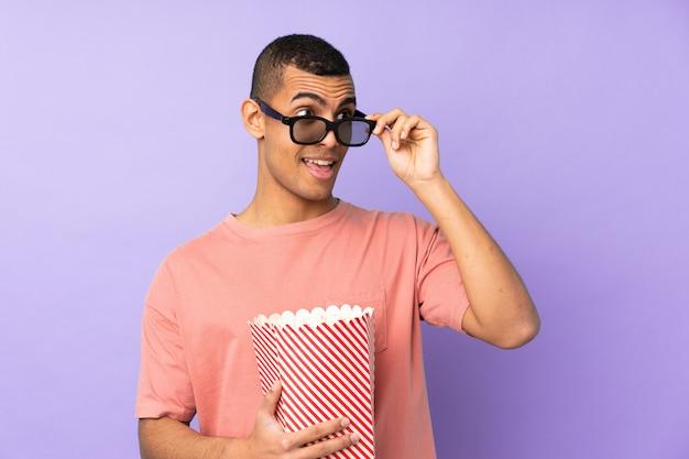 3 dメガネとポップコーンの大きなバケツを保持している分離の青い壁の上の若いアフリカ系アメリカ人の男