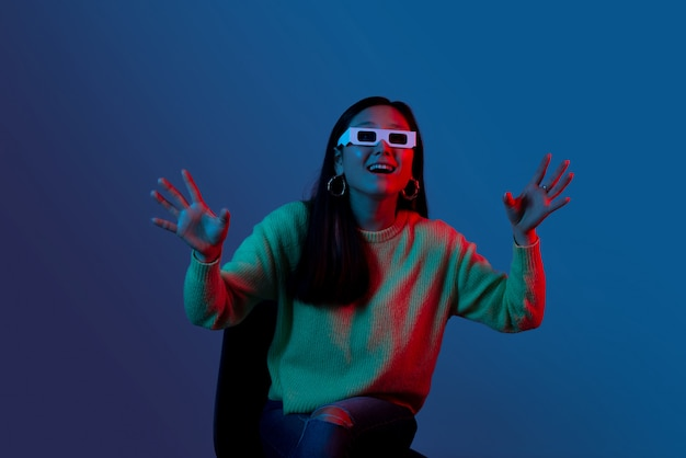 青と赤の光の中で映画3 dメガネを着て興奮している女性