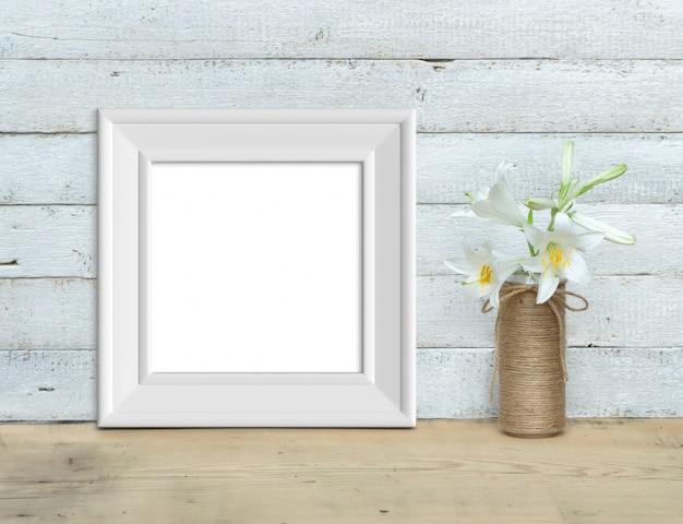 ユリの花束の近くの正方形のビンテージホワイト木製フレームモックアップは、塗られた白い木製の背景に木製のテーブルの上に立っています。素朴なスタイル、シンプルな美しさ。 3 dのレンダリング。