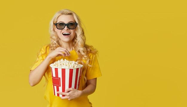 3 dメガネとポップコーンを食べる黄色のシャツで驚いた若いブロンドの女性は、映画館で衝撃的な映画に見えます。孤立した