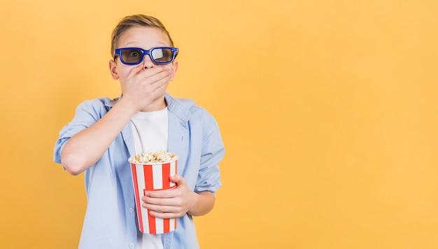 黄色の背景に手で立ってポップコーンバケツを保持している3 dメガネをかけてショックを受けた少年