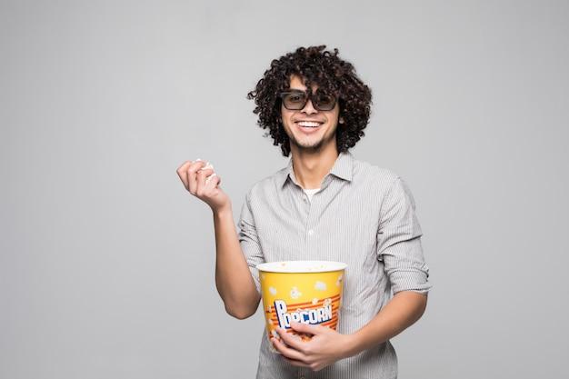 若いハンサムな男は孤立した白い壁にポップコーンのボウルを保持している巻き毛の3 dメガネを着用します。