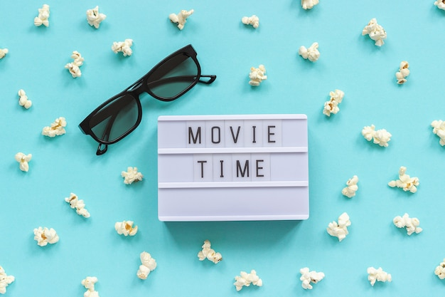 3 dメガネ、ポップコーンとライトボックスのテキスト青い紙の背景に映画の時間。