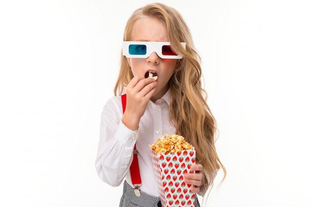 Маленькая девочка с длинными светлыми волосами в очках 3-d ест попкорн.