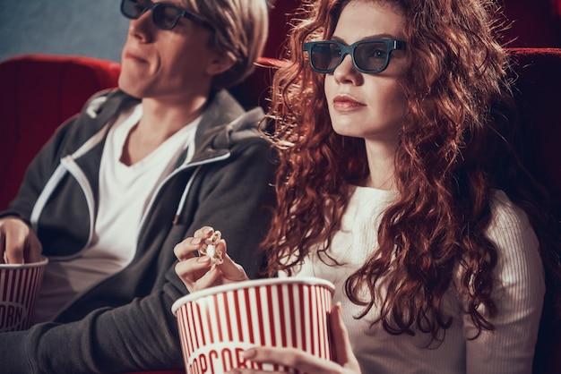 3 dメガネとカップルは、ポップコーンを食べたり、映画館に座っています。