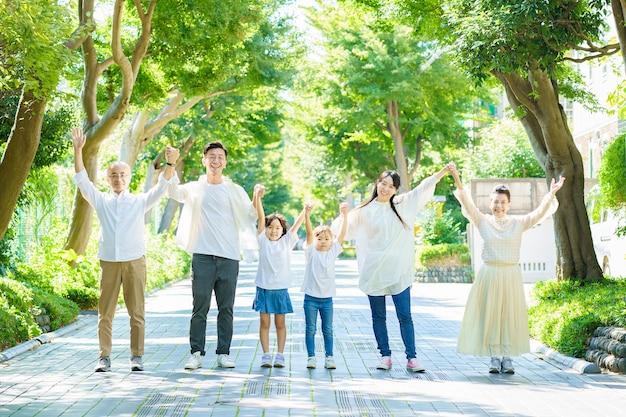 緑豊かな通りで手をつないで3世代家族