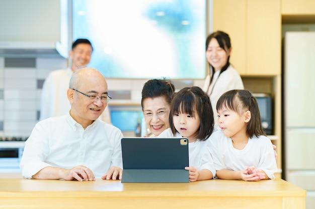 テーブルの上のタブレットpcで遊ぶ3世代家族