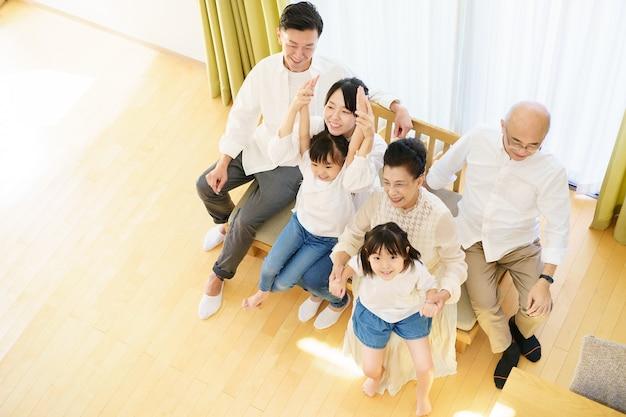 Семья в 3-м поколении сидит на диване в комнате