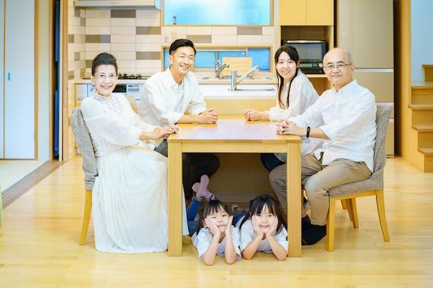 部屋のテーブルに集まる3世代家族