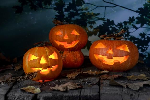 夜の神秘的な森の木製テーブルの上の3つのハロウィーンカボチャ頭ジャックoランタン。ハロウィンデザイン