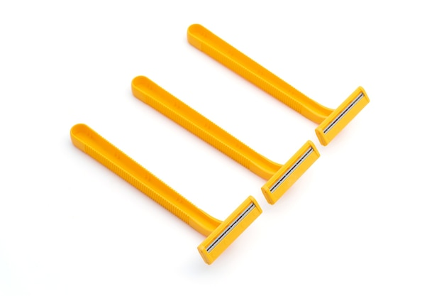 흰색 배경에 분리된 3개의 트윈 블레이드 노란색 일회용 면도기.