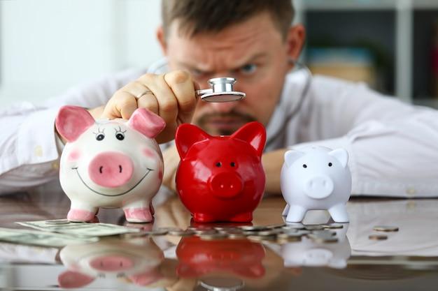 Рука бизнесмена с стетоскопом рассматривая 3 piggybanks