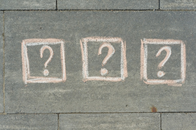 3 question marks painted on the grey sidewalk
