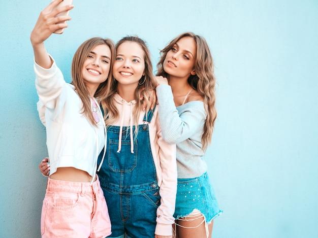 夏服の3人の若い笑顔の流行に敏感な女性。スマートフォンでselfieセルフポートレート写真を撮る女の子。壁の近くの通りでポーズをとるモデル。肯定的な顔の感情を示す女性