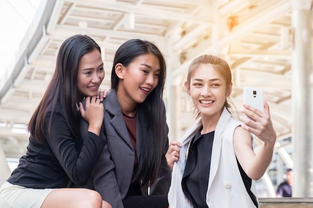 3つのかわいいアジアの女性はselfieであり、面白い女の子は自分で写真を撮ります。