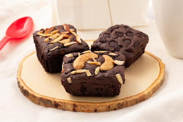 木製の受け皿にチョコレートチップ、アーモンド、ナッツ、ティータイム、コーヒータイム、または休憩タイム用のスイーツが入った3つの正方形のダークブラウニー。