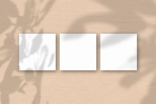 3 квадратных листа белой текстурированной бумаги на оранжевом фоне стены. наложение мокапа с тенями растений. естественный свет отбрасывает тени от тропических растений .. плоская планировка, вид сверху. горизонтальная ориентация