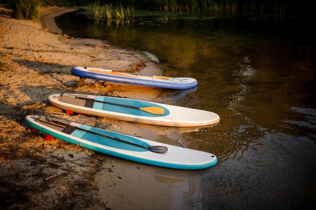 夕日の湖畔の水の近くに横たわっている3つのsupボード