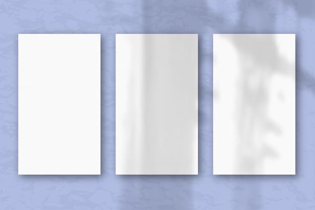 3 вертикальных листа текстурированной белой бумаги на нежно-голубом фоне стола, естественный свет отбрасывает тени из окна. горизонтальная ориентация.