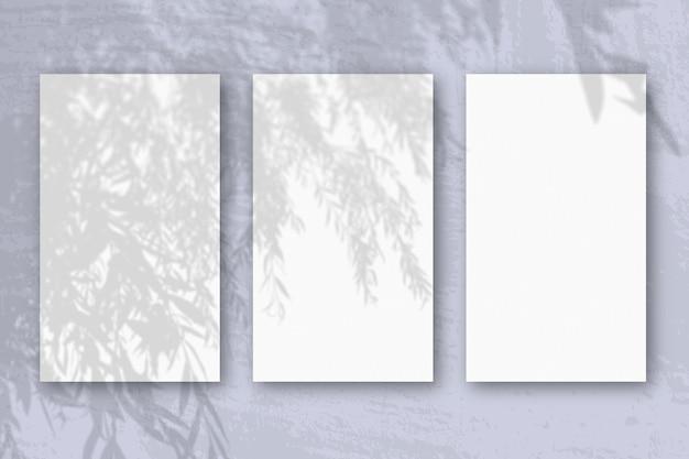 3 вертикальных листа текстурированной белой бумаги на мягком синем столе
