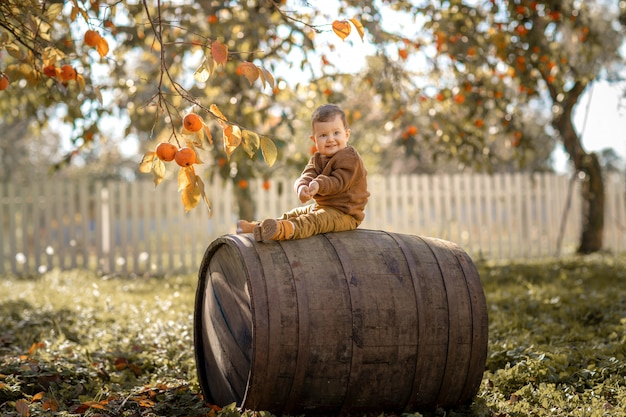 A 3-year-old boy sits on a large wooden barrel