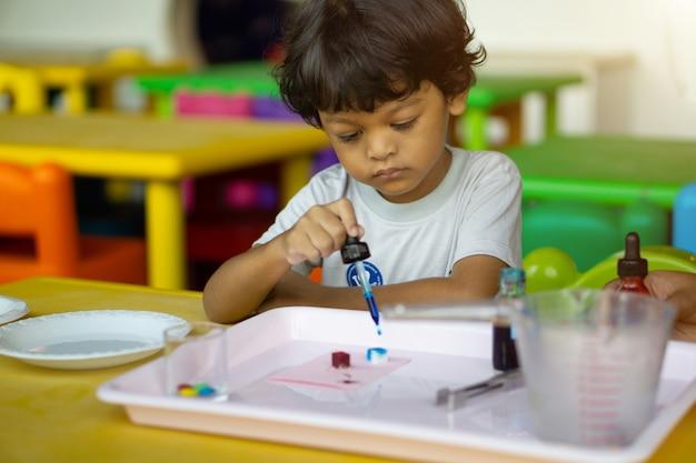アジアの3歳の子供たちが科学実験を行っています。