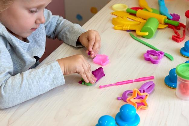 3歳の女の子のクリエイティブアート。カラフルな粘土の粘土で遊ぶ子供の手。自己隔離covid-19、オンライン教育、ホームスクーリング。家で勉強している幼児の女の子、家の学習