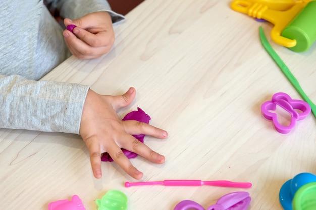 3歳の女の子のクリエイティブアート。カラフルな粘土の粘土で遊ぶ子供の手。自己隔離covid-19、オンライン教育、ホームスクーリング。家で勉強している幼児の女の子、家の学習。