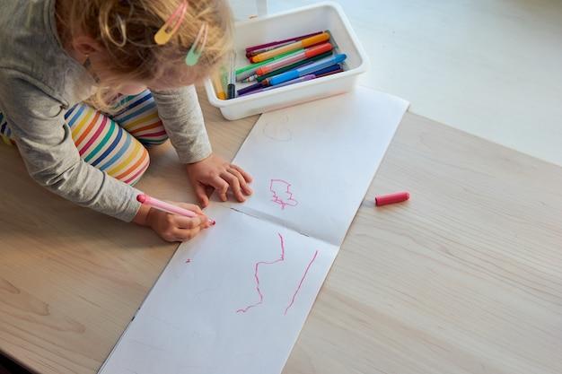 3 года девочка творчества. ребенок рисует картинку. детский сад и дошкольное учреждение закрыты на период covid-19, онлайн-обучение, домашнее обучение. девочка малыша учится дома, домашнее обучение.
